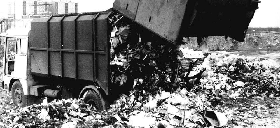 Historische Aufnahme eines Müllwagens beim Müll abladen